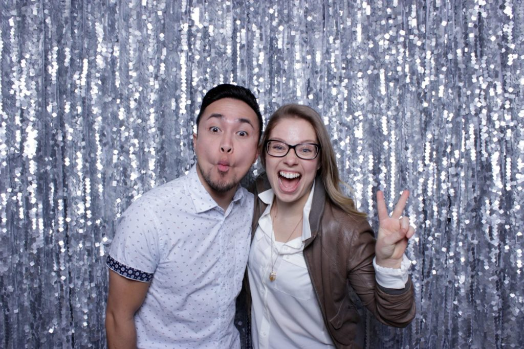 A man making a funny face and a woman smiling with her hand in a peace sign in front of a glittery backdrop