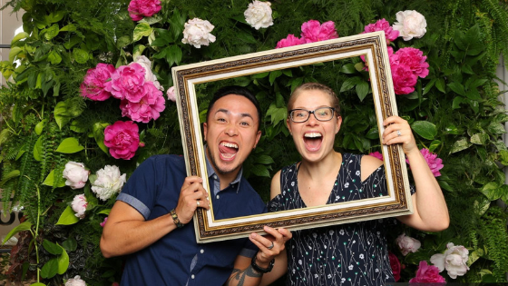 A man and woman smiling through a frame in front of a flower wall because they are debt free and married in love.