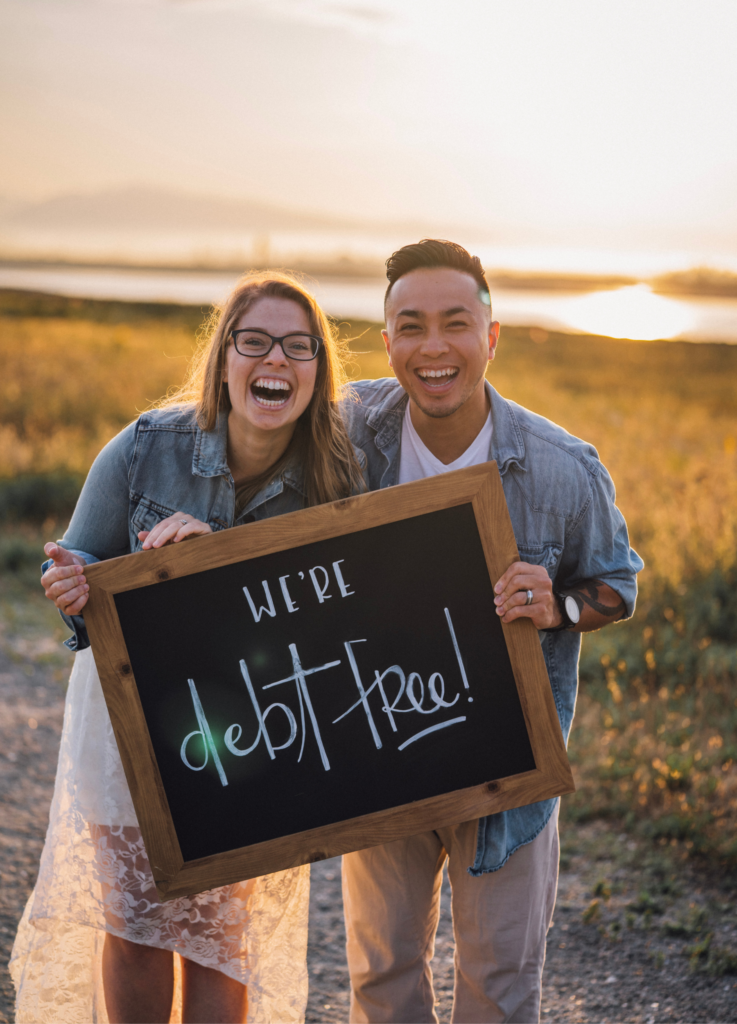 "A married couple holding a sign that say's, ""we're debt free!"" at sunset"